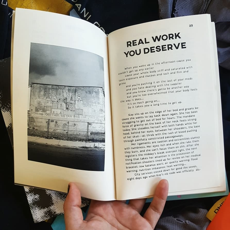 Im holding open the zine. A b/w image of a building with a mural on it is on the left. The right has a story titled REAL WORK YOU DESERVE.