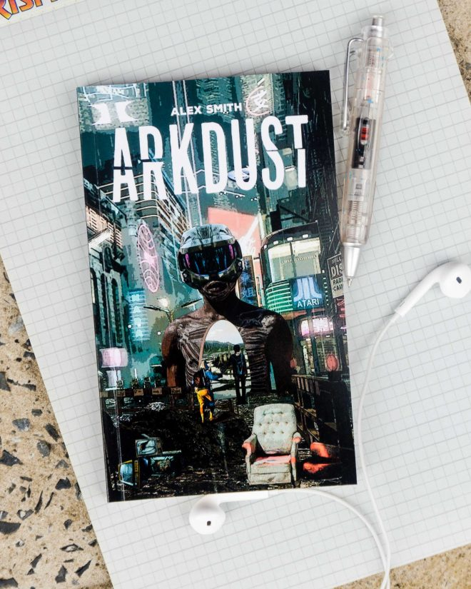 The compact ARKDUST book with vibrant cyberpunk styled cover laying on top of a legal pad with pen and headphones nearby
