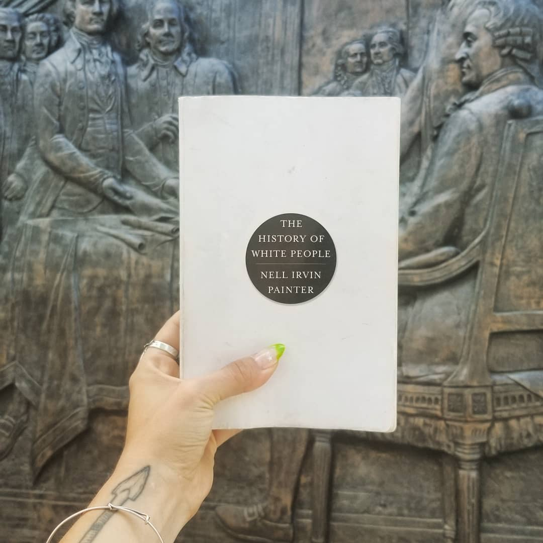A white mixed race person's hand holds a white book with black circle on the cover in front of a bronze relief of the Founding Fathers
