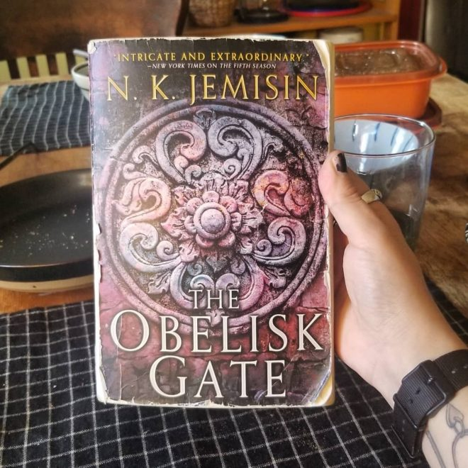 me holding up the Obelisk Gate book over my kitchen table