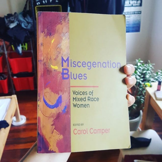 My hand holding up the cover of Miscegenation Blues