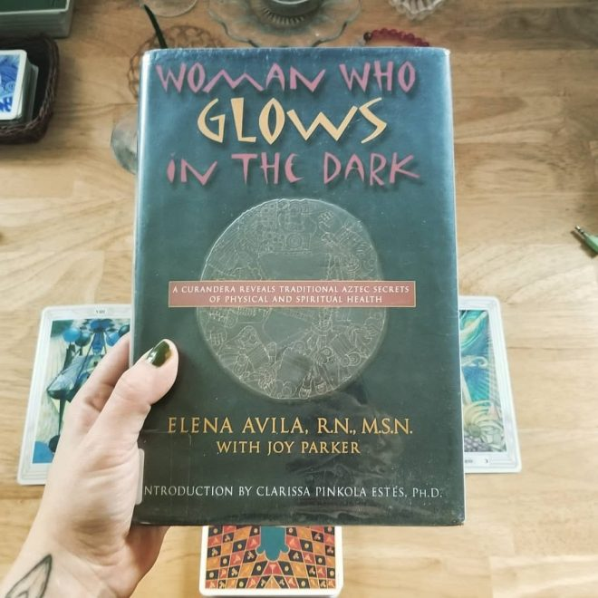 My left hand holding Woman Who Glows in the Dark over my table with a tarot spread beneath