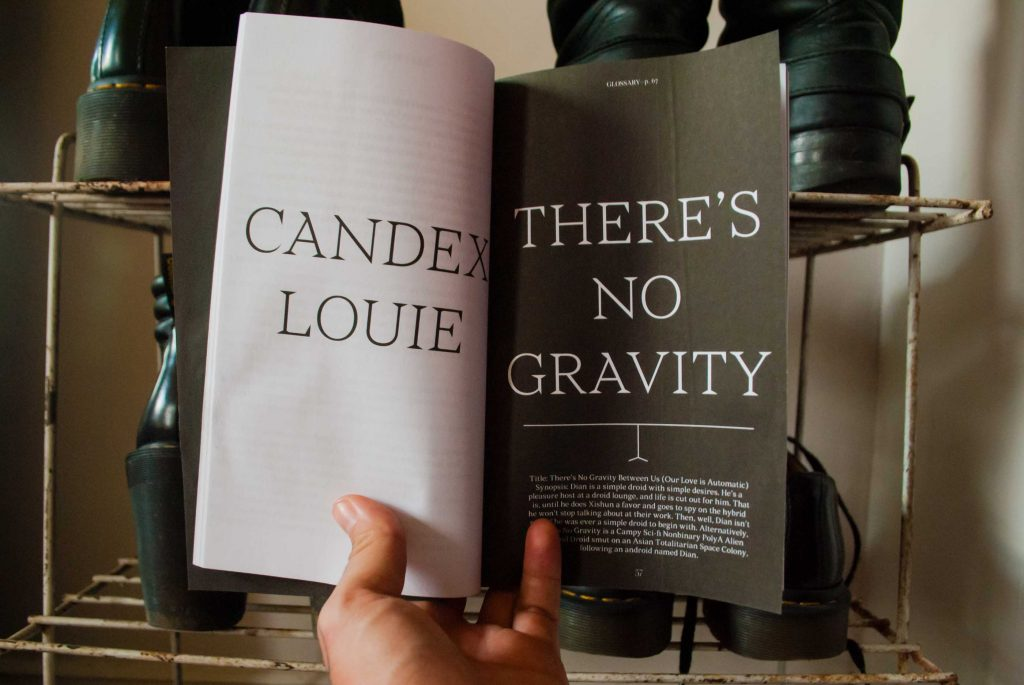 me holding the book open to a dramatic high contrast title page that says CANDEX LOUIE on the left and THERE'S NO GRAVITY on the right