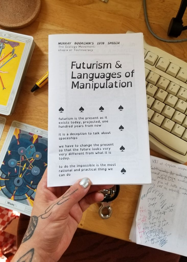 My left hands hold the booklet zine , with my keyboard and some tarot cards on my desk in the background. The zine says FUTURISM & LANGUAGES OF MANIPULATION