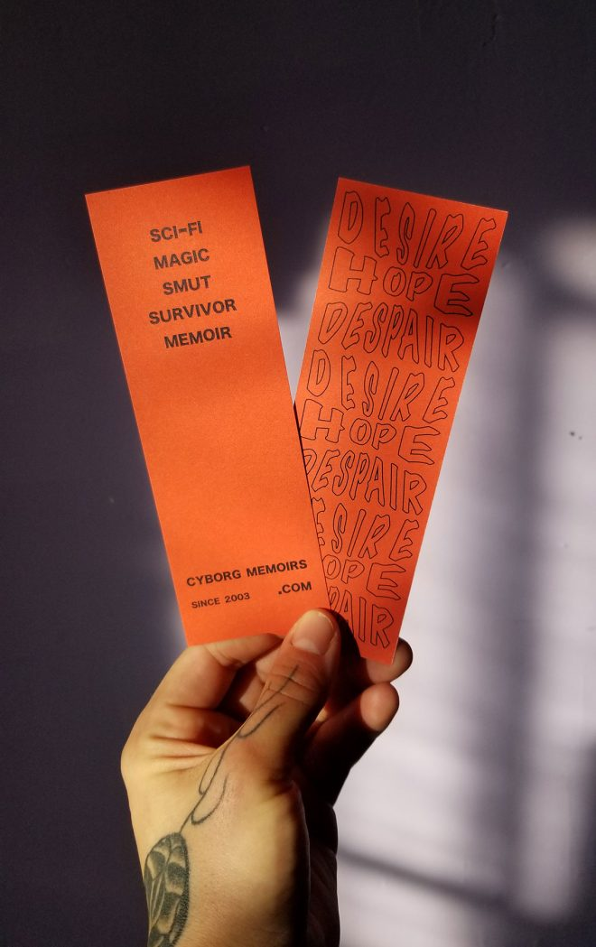 my left hand holding up 2 bookmarks, showing both sides of the same design. The front says scifi magic smut survivor memoir / cyborgmemoirs.com since 2003. The back has a stylized repeating logo design that says desire hope despair. Black ink on brick red.
