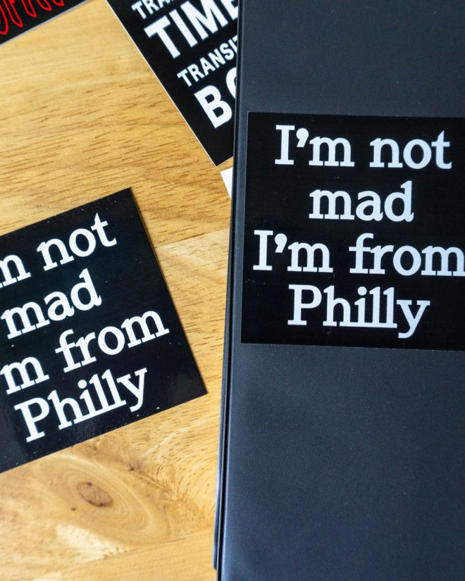 A close-up of a notebook cover and 2 stickers on a wood table. The sticker says I'M NOT MAD I'M FROM PHILLY.