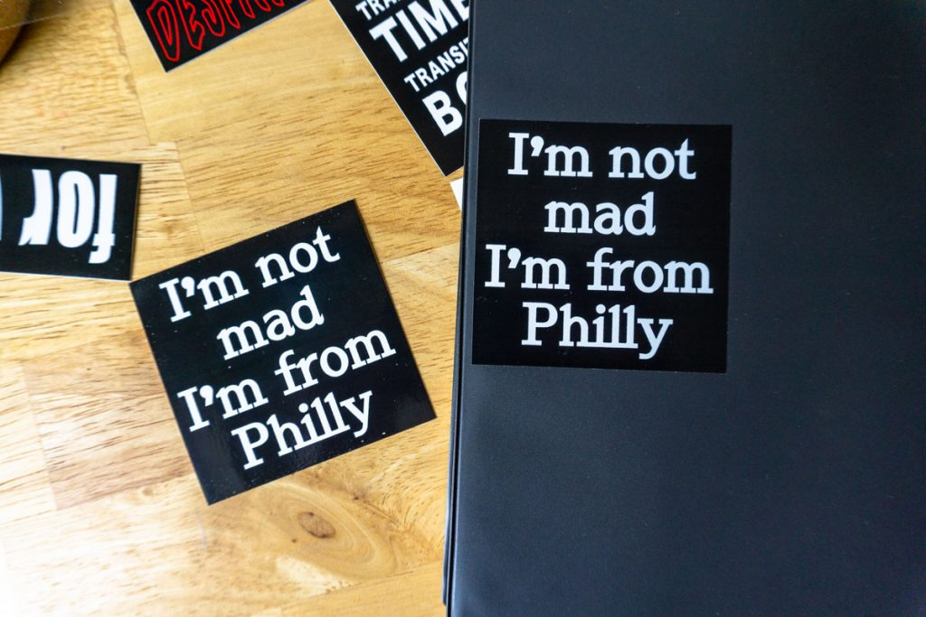 """stickers on a wood table. they read """"I'm not mad I'm from Philly"""""""